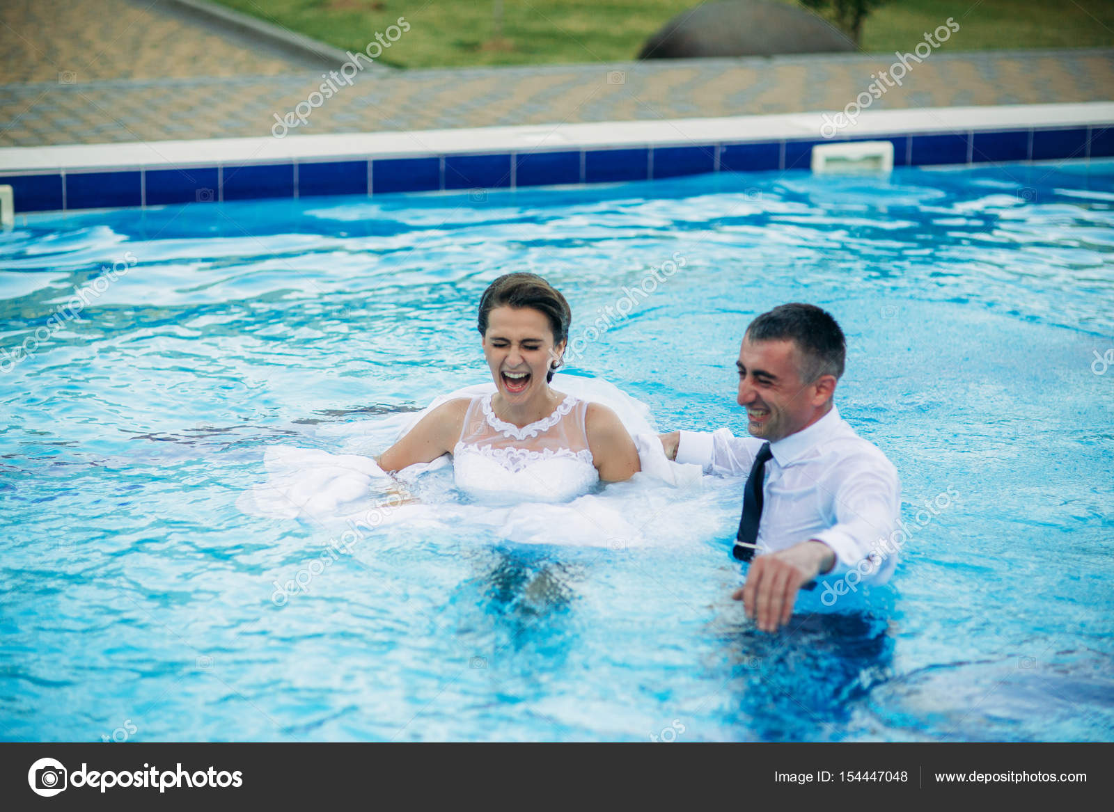 young couple jumping in the swimming pool in a wedding suit and wedding dress sunny day. Black Bedroom Furniture Sets. Home Design Ideas