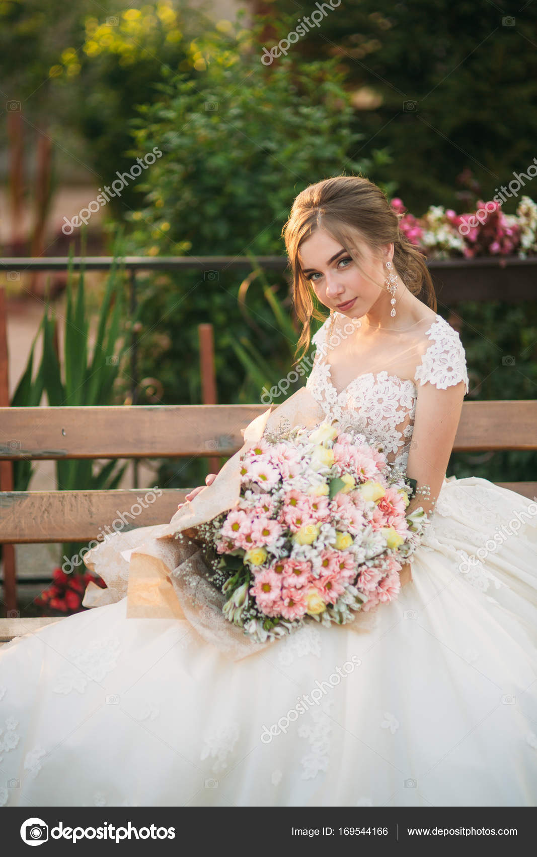 Young girl in wedding dress in park posing for photographer. Sunny ...