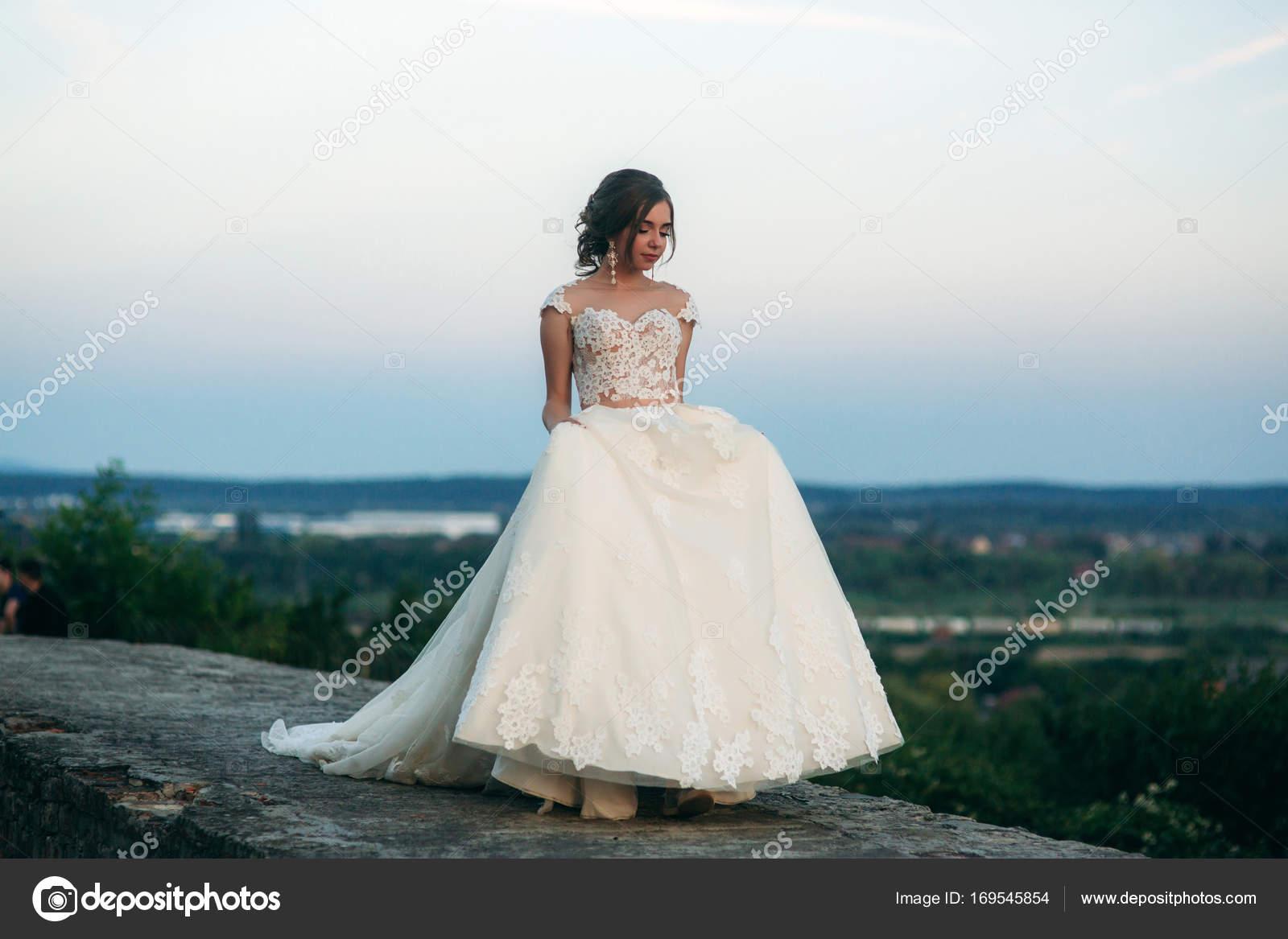 Niña en vestido de novia en el fondo de la ciudad al atardecer ...
