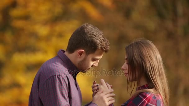 A loving couple walks in the autumn in the park. A love story on a sunny autumn day. lake and bringe .