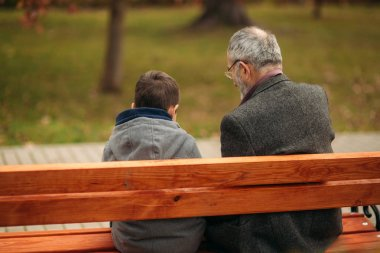 Grandpa and his grandson spend time together in the park. They are sitting on the bench. Walking in the park and rejoicing