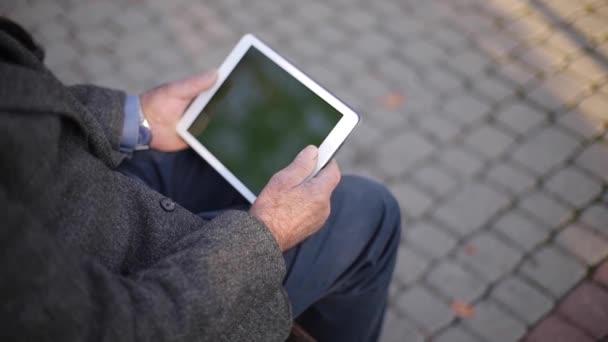 Attrappe eines älteren Mannes mit Tablet draußen. Rückansicht eines älteren Mannes, der auf der Bank sitzt und Tablet benutzt