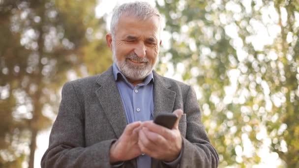 Nahaufnahme eines alten Mannes mit weißem Bart, der sein Smartphone draußen benutzt