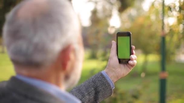 Kigúnyolják az idős embereket, akik odakint telefonálnak. Zöld vászon. Visszapillantás a férfira, aki a telefont tartja. Nagypapa forgatás videó okostelefon