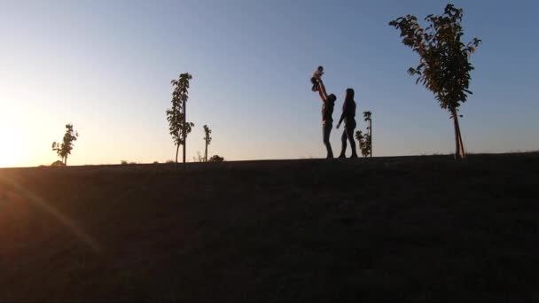 Silhouette of mom dad and daughter walking in the park though the embakment. Happy family spend time together