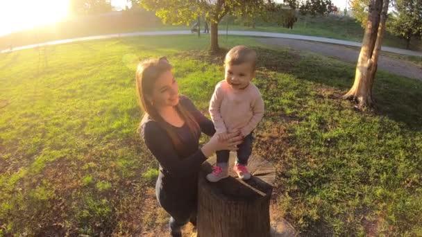 Rozkošná holčička, procházející se v říjnu v parku s mámou. Roztomilá desetiměsíční procházka. Krásná šťastná dívka. Podzimní nálada