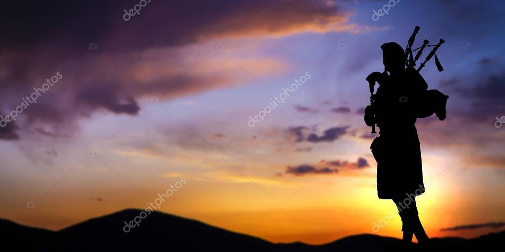 Bagpipe player in silhouette over sunset