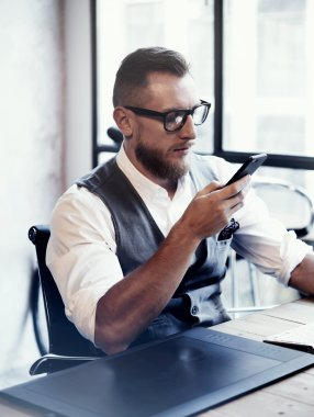 Bearded Stylish Young Man Wearing Glasses White Shirt Waistcoat Working Modern Loft Startup Process.Creative Person Using Smartphone Texting Message.Drawing Tablet Desktop Computer Wood Table.Vertical