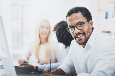 Dark skinned entrepreneur wearing glasses, working in modern office.African american man in white shirt looking and smiling at the camera.Horizontal,blurred background