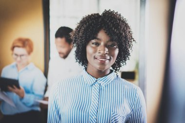 Portrait of young african woman with afro looking and smiling at the camera.Business team on background in modern office. Horizontal,blurred.