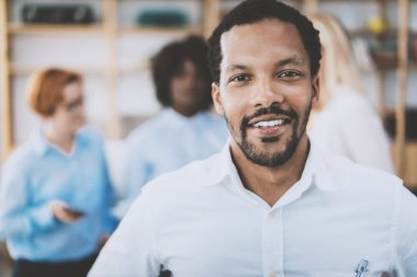 Portrait of african american man looking and smiling at the camera.Business team on a background in modern office. Horizontal,blurred .