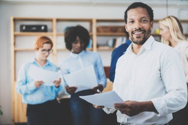 African american entrepreneur in white shirt holding papers in hands and smiling at the camera.Teamwork concept in modern office. Horizontal,blurred background.