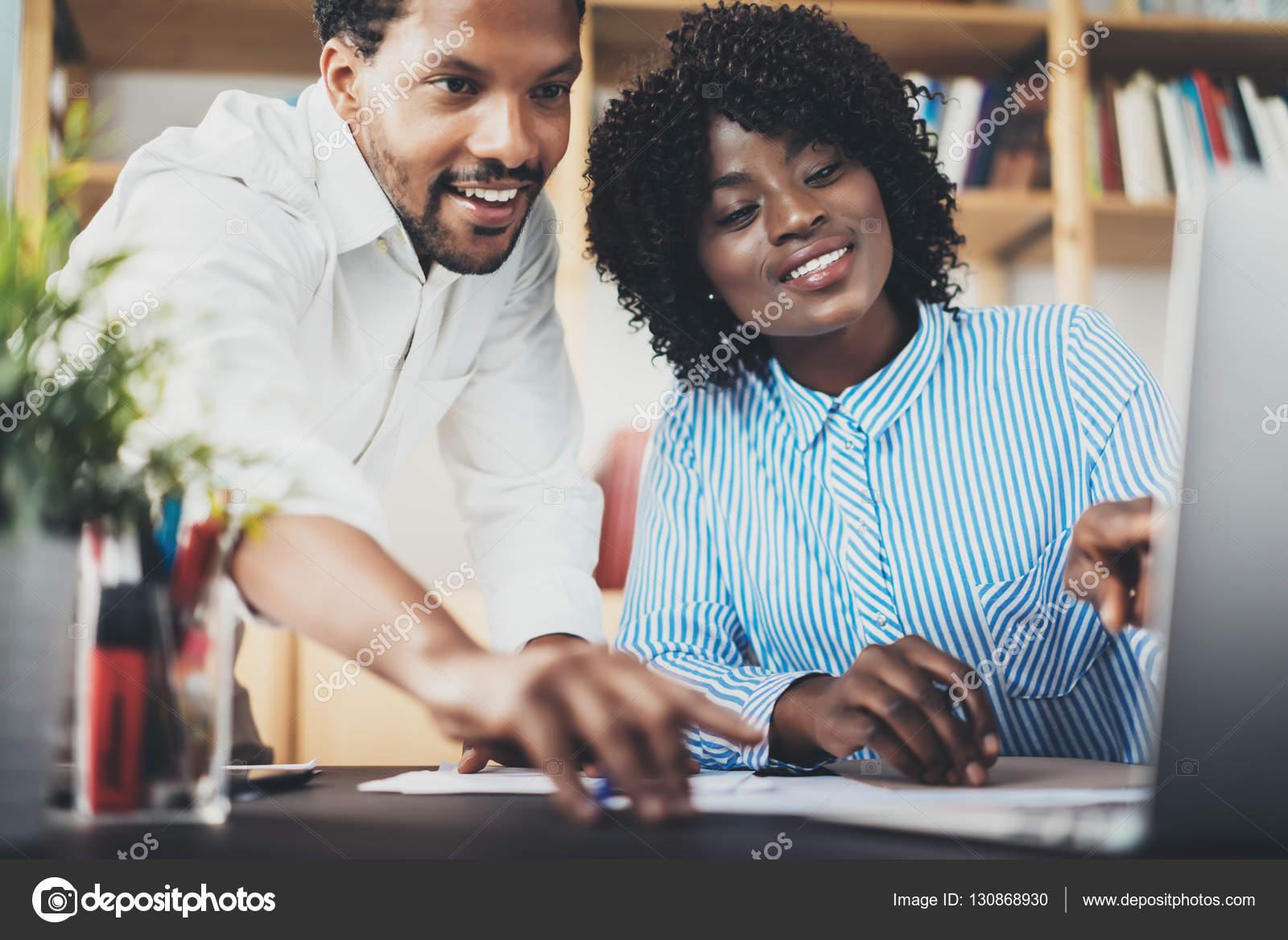 Deux jeunes collaborateurs travaillant ensemble dans un bureau