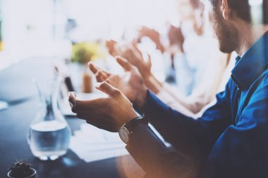 Close up view of young business partners applauding to reporter after listening speech at seminar. Professional education, work meeting, presentation or coaching concept.Horizontal,blurred background.