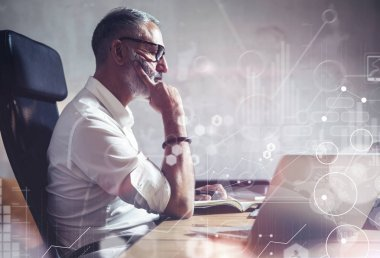 Concept of adult bearded businessman making a great business decisions in modern workplace.Screen global virtual icon,diagram and graph interfaces.Horizontal, flares effect, blurred.