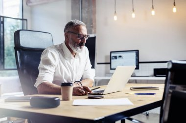 Adult professional businessman wearing a classic glasses and working at the wood table in modern coworking studio.Stylish bearded middle age man using laptop on workplace. Horizontal,blurred.