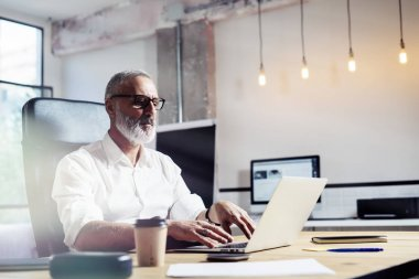 Middle age financial analyst wearing a classic glasses and working at the wood table in modern interior design office.Stylish bearded businessman using laptop on workplace. Horizontal,blurred.