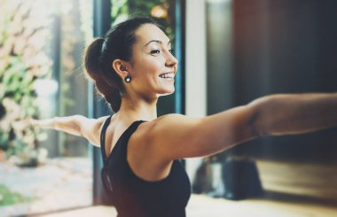 Portrait of gorgeous young woman practicing yoga indoor. Beautiful girl practice Warrior Light asana.Calmness and relax, female happiness.Horizontal, blurred background.