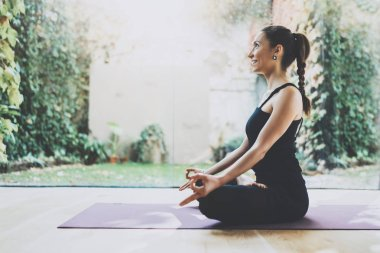 Portrait of gorgeous young woman practicing yoga indoor. Beautiful girl practice lotus position in class.Calmness and relax, female happiness.Horizontal, blurred background.