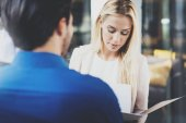 Two coworkers discussing business strategy in modern office.Successful confident hispanic businessman talking with blonde woman. Horizontal, blurred background.