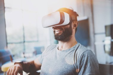 Bearded man wearing virtual reality glasses in modern interior design coworking studio. Smartphone using with VR goggles headset. Horizontal,film effect, blurred background.