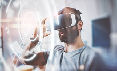 Concept of digital screen,connection interfaces.Bearded man wearing virtual reality glasses in modern interior design coworking studio. Smartphone using with VR goggles headset.Blurred background.