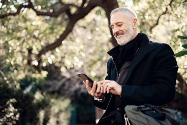 Happy adult attractive businessman texting message on mobile phone while sitting in city park at sunny day.Horizontal,blurred background.