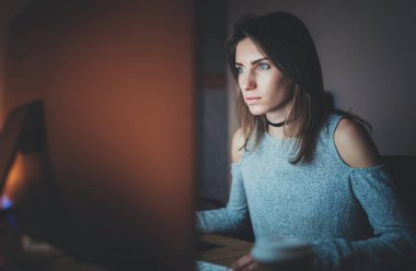 Young beautiful woman working on modern loft office at night. Girl using contemporary desktop computer, blurred background. Horizontal, film effect.