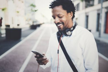 Happy smiling African man using smartphone outdoor.Portrait of young black cheerful man texting a sms message with friends.Blurred background.