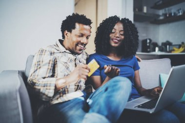 Happy young african american couple sitting on sofa at home and shopping online through mobile computer by credit card. Horizontal,blurred background.
