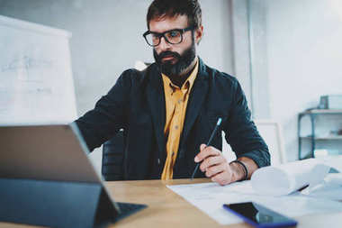 Cropped photo of young bearded male architect wearing eye glasses working on digital tablet dock at his desk. Professional experienced engineer constructionist developer.Horizontal.Blurred background.