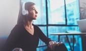 Fotografia Bella ragazza bionda che indossa occhiali e casual clothes digitale ascolto musica in cuffie su smartphone mentre ci si rilassa in poltrona a posto moderno