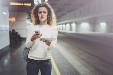 Beautiful girl happy using mobile phone app for conversation in holiday travel.Pretty woman on transit platform using mobile phone while waiting rail train on station.