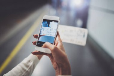 Closeup view of girl on transit platform using smartphone for make photo of train ticket while waiting rail train on metro station.