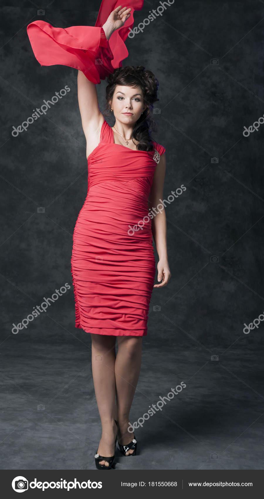 33fa7003c4 Egy bájos barna a divatos elegáns piros ruha teszi bemocskolják a  stúdió-fekete háttér — Fotó szerzőtől ...