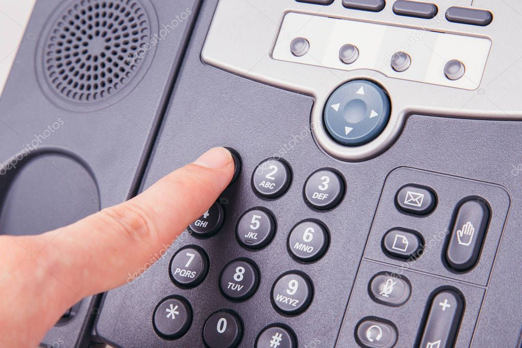 Finger pressing number button on telephone to make a call
