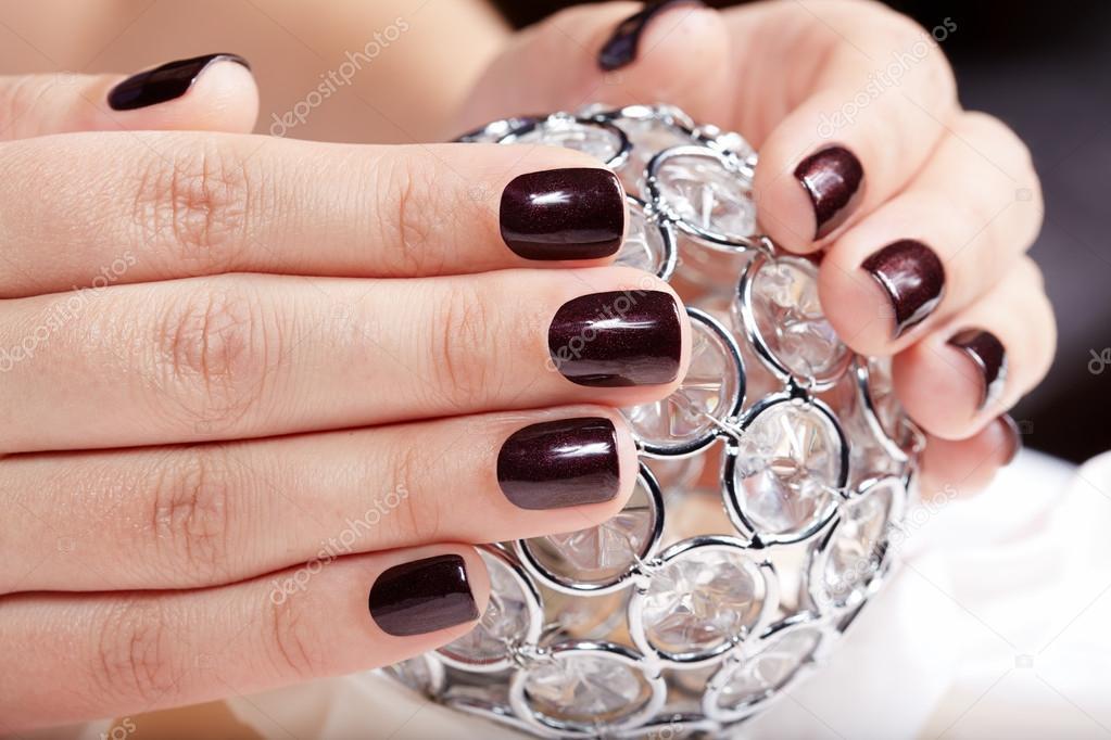 Manos con uñas cuidadas de color con esmalte de uñas morado oscuro ...