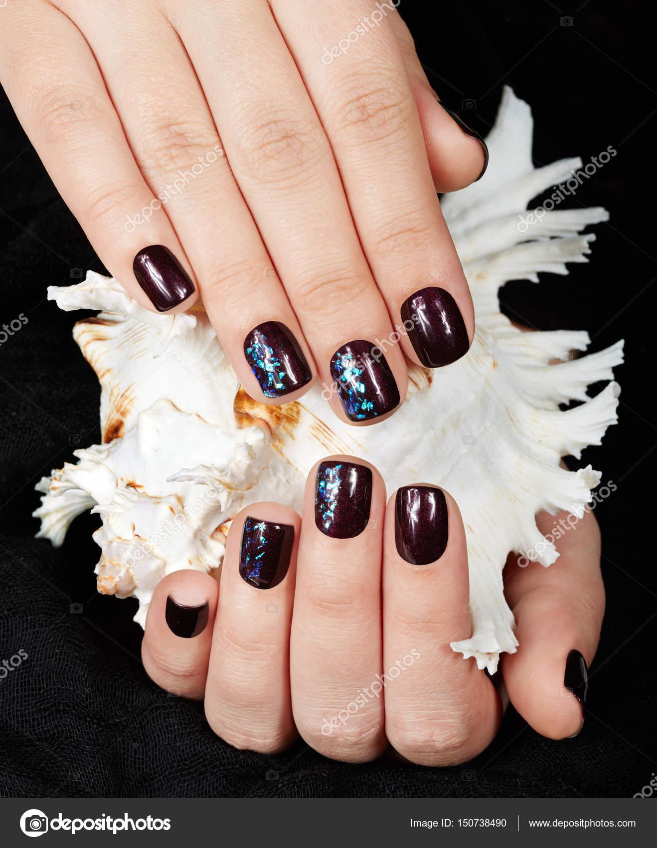 Manos con corta uñas cuidadas de color con esmalte de uñas morado ...
