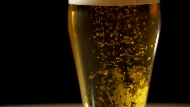 Nahaufnahme eines Glases mit Bier, das isoliert ausgeschenkt wird