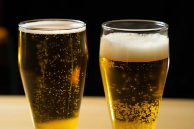 Close-up of goblets with pouring beer on black background