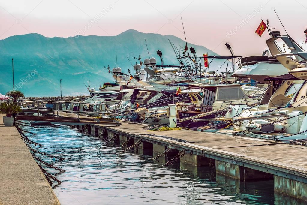Budva, Montenegro - August 28, 2017:  Pier for sailing yachts and boats with a view of the mountains off the coast of Budva, Montenegro.