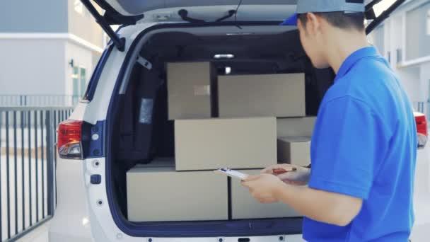 Doručovatel vzít balíček z kufru zasílání balíků poštovní zásilky objednávky přijde k zákazníkovi v předním domě otevřené dveře, Doručení balíček služby. 4k Uhd záběry kinematografie