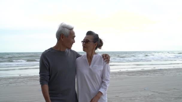 Asijské pár senior starší důchodce odpočinek relax chůze při západu slunce pláž líbánky rodina spolu štěstí lidé životní styl, Zpomalený film záběry