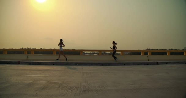 SLOW MOTION, Partners women Running marathon near river water summer sunset, Athlete fit jogs exercise runners professional outdoor at beautiful nature healthy lifestyle