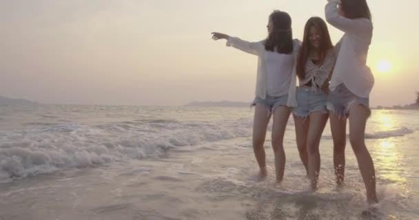 Gülümseyen Asyalı arkadaş grubu sahilde birlikte yürüyorlar yaz tatilinde gün batımında siluet gün batımında bayram tatili hayatın tadını çıkar hafta sonu aktiviteleri insanların yaşam tarzı, yavaş çekim 4K