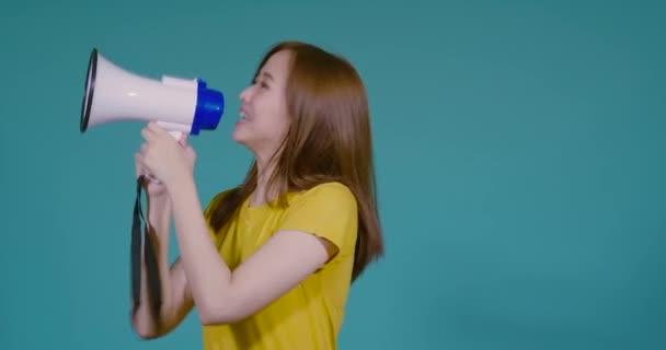Mluvení Hlasitý šum oznámení mladé asijské ženy s megafonem ve žlutém tričku usmívající se emoce na modrém pozadí izolované studio shot
