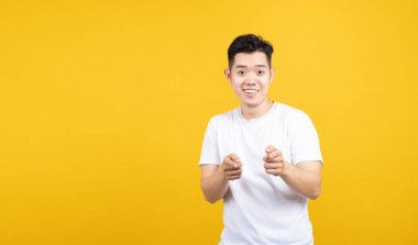 Attractive portrait happy young asian man gald excited emotion smiling looking at camera with copy space wearing white t-shirt on yellow background isolated studio shot