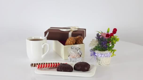 cookies with tea cup and gift box on spinning table background