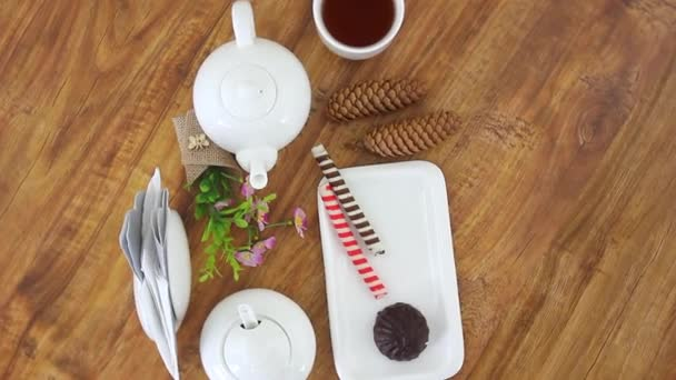 top view spinning video of kettle with tea cup and sweet sticks with marshmallow on wooden table background