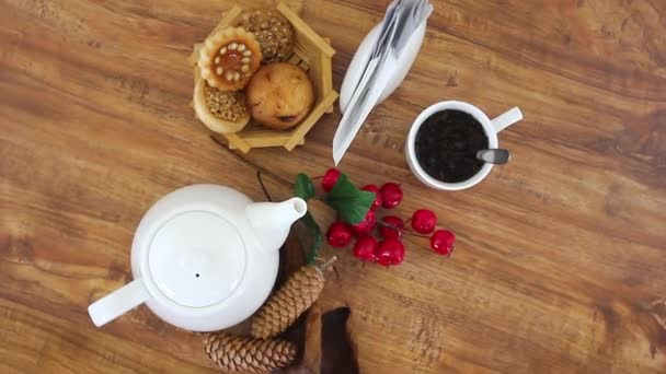 vrchní pohled točení videa bílé konvice s čajovým šálkem a košíkem se sušenkami